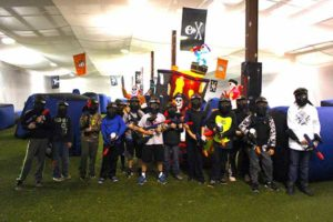 large group of boys with paintball guns and paintball masks